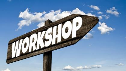 "Directional sign with ""Workshop"" written across it against blue sky with clouds"