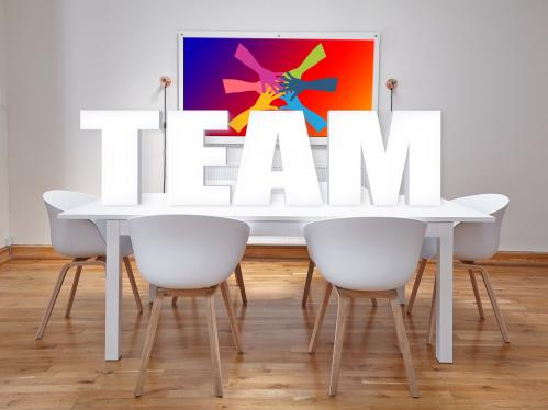 White conference room table with large TEAM in block letters on top